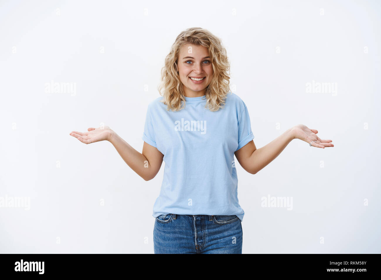 I do not know. Portrait of silly and cute blond european female with blue eyes making shoulder shrugg with hands spread sideways and smiling shy as - Stock Image