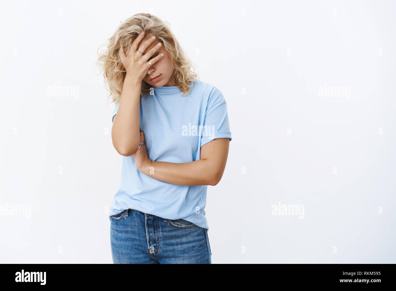 Oh God what humiliation. Portrait of fed up drained and distressed young woman making facepalm holding hand on face with disappointment, posing - Stock Image