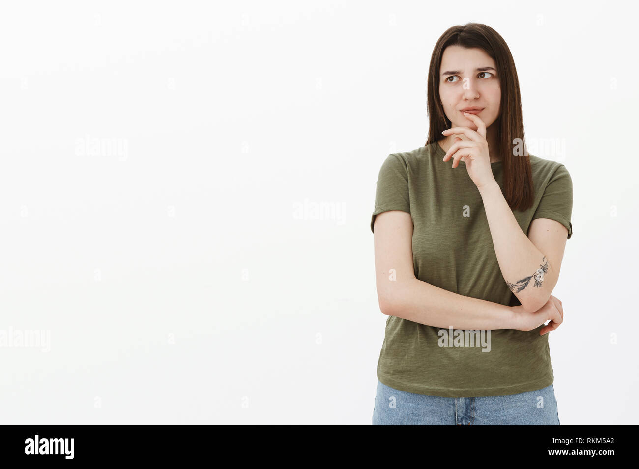 Hmm need think about it. Portrait of thoughtful focused smart and creative female coworker with tattoo doing brainstorm making up idea looking at - Stock Image