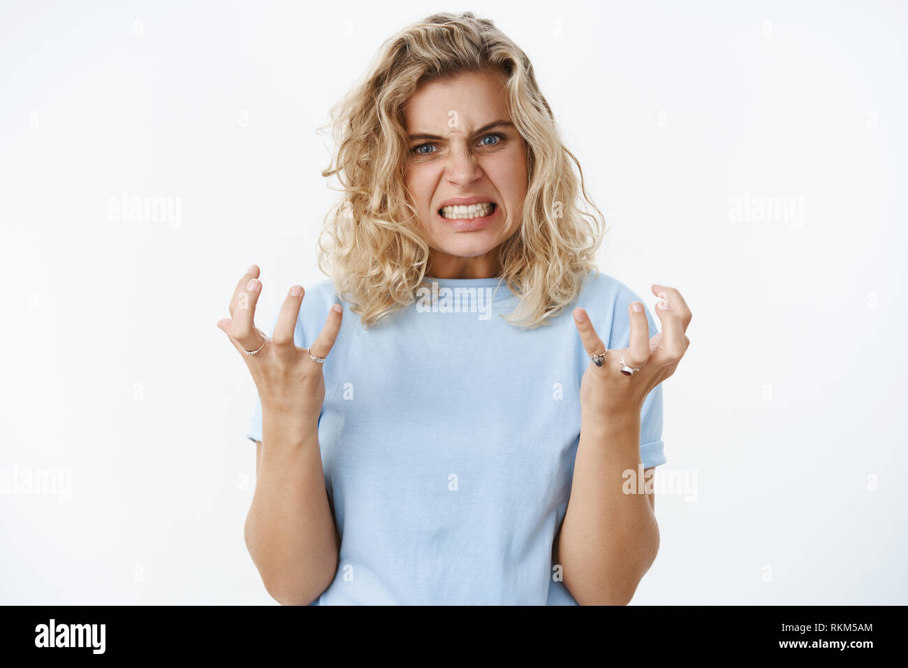 Girl gonna blow out over anger and distress clench teeth and fists in fury and dismay frowning being pressured and distressed full of hate, looking - Stock Image