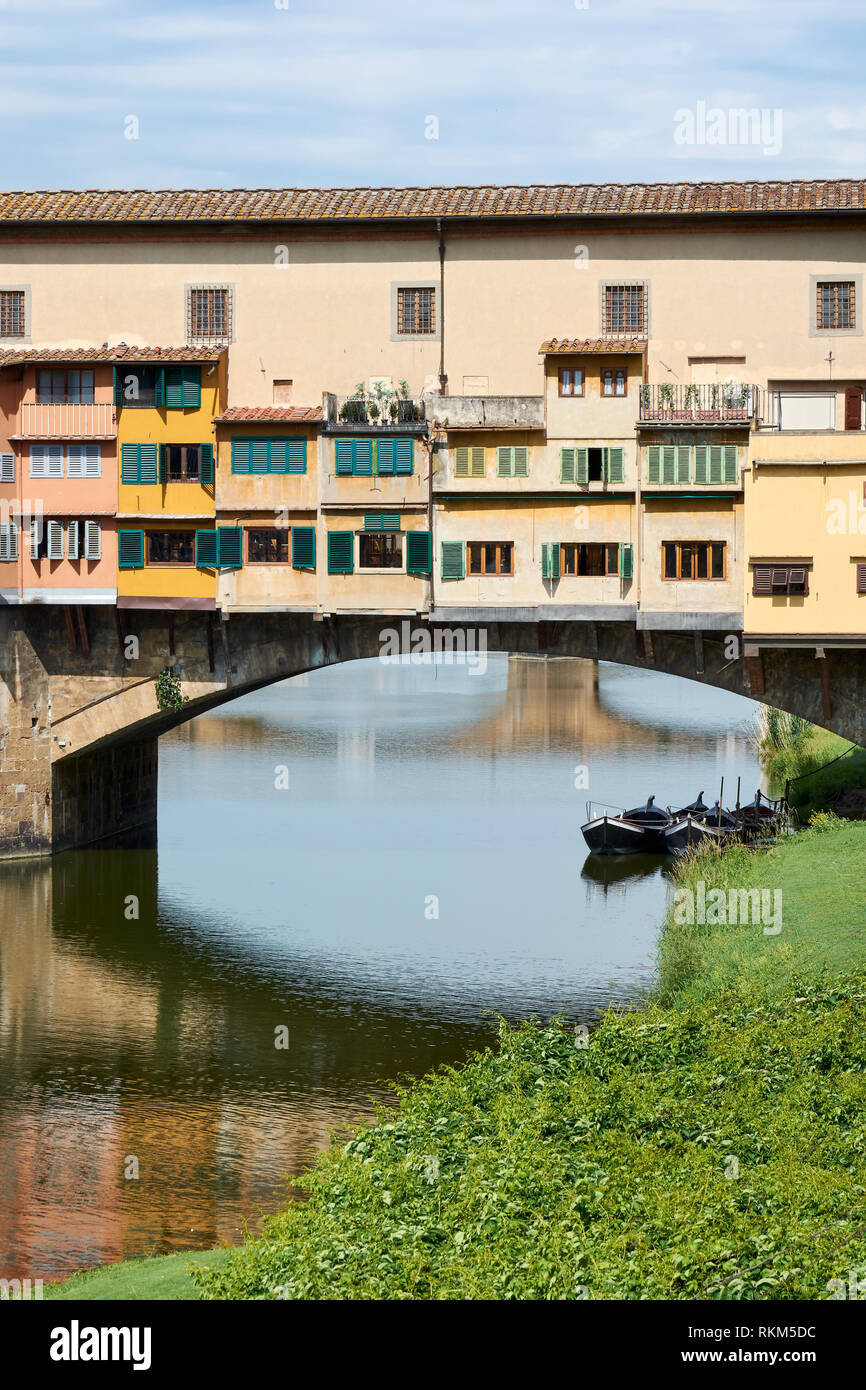 Closeup and details of the medieval stone bridge called Ponte Vecchio in Florence, Italy, on a sunny spring day, with the reflection of Ponte Santa Tr - Stock Image