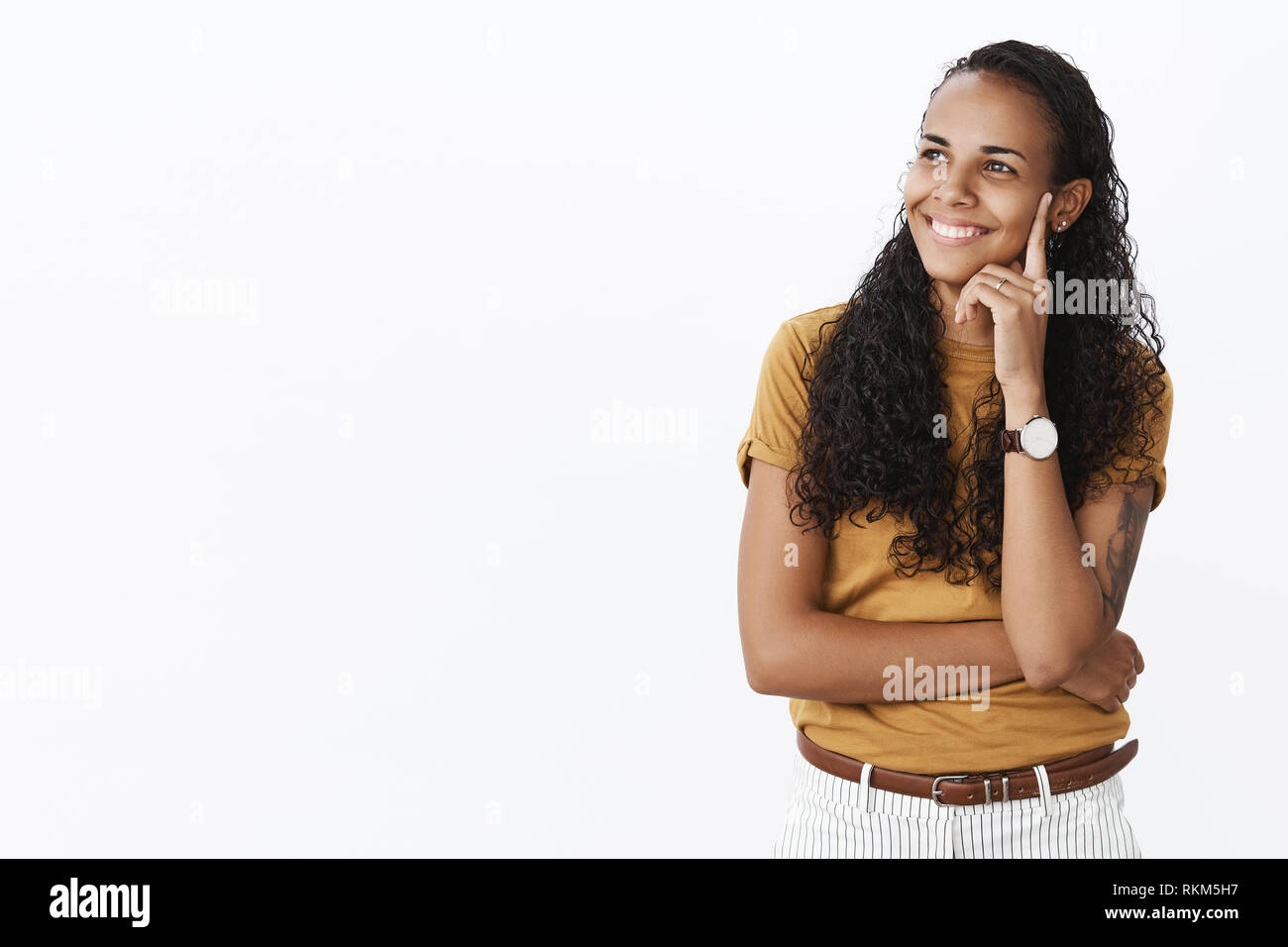 Indoor shot of happy carefree charming african-american delighted woman in t-shirt holding finger on temple smiling satisfied as gazing left nostalgic - Stock Image