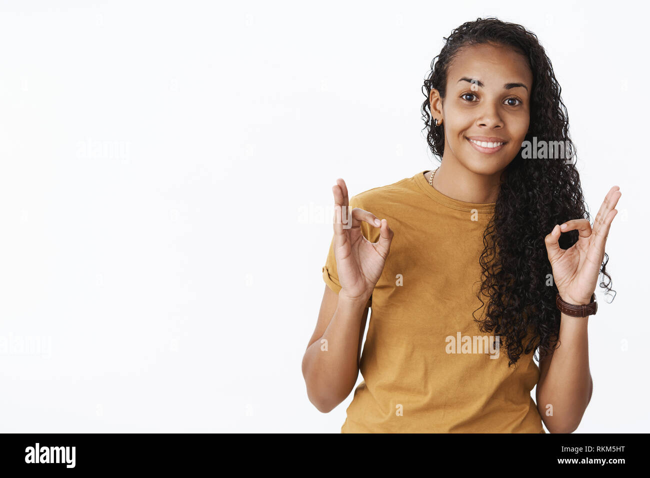 Nice, I agree. Portrait of friendly and satisfied young kind african-american female friend cheering and being supportive showing okay gesture being - Stock Image