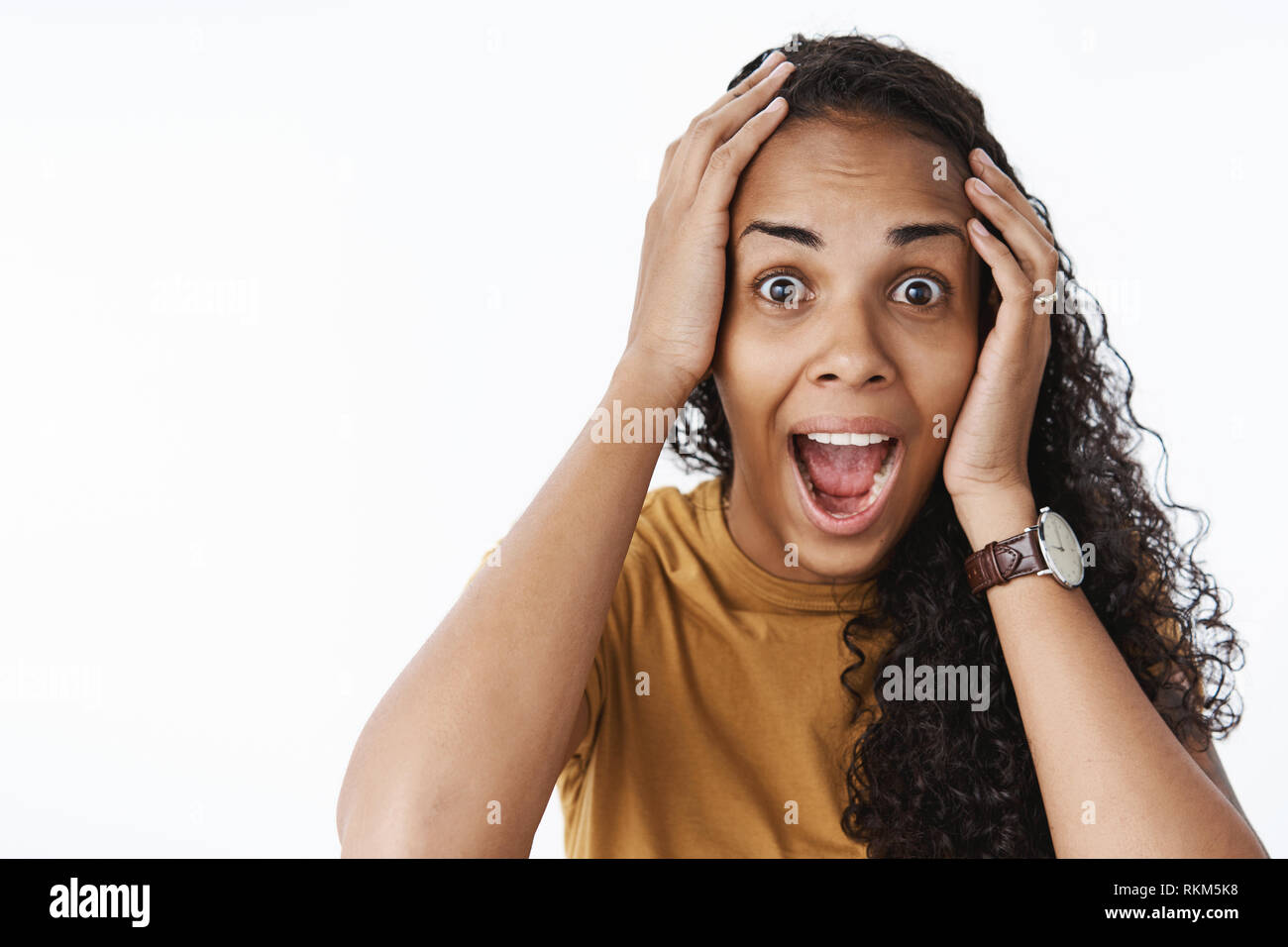 Close-up shot of thrilled astonished happy african-american woman with curly hair dropping jaw yelling from excitement and joy holding hands on head - Stock Image