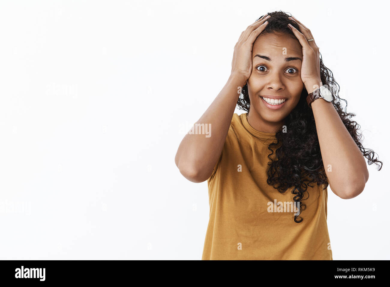 Waist-up shot of surprised happy woman reacting to unbelievable luck grabbing head with hands and smiling broadly being thrilled and excited as - Stock Image