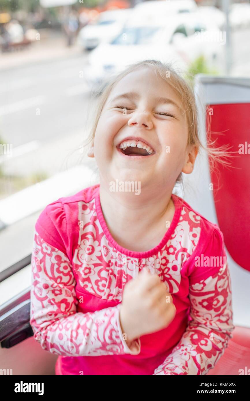 Portrait of funny four years old girl, with pink shirt, laughing out loud, open mouth, on bus. - Stock Image
