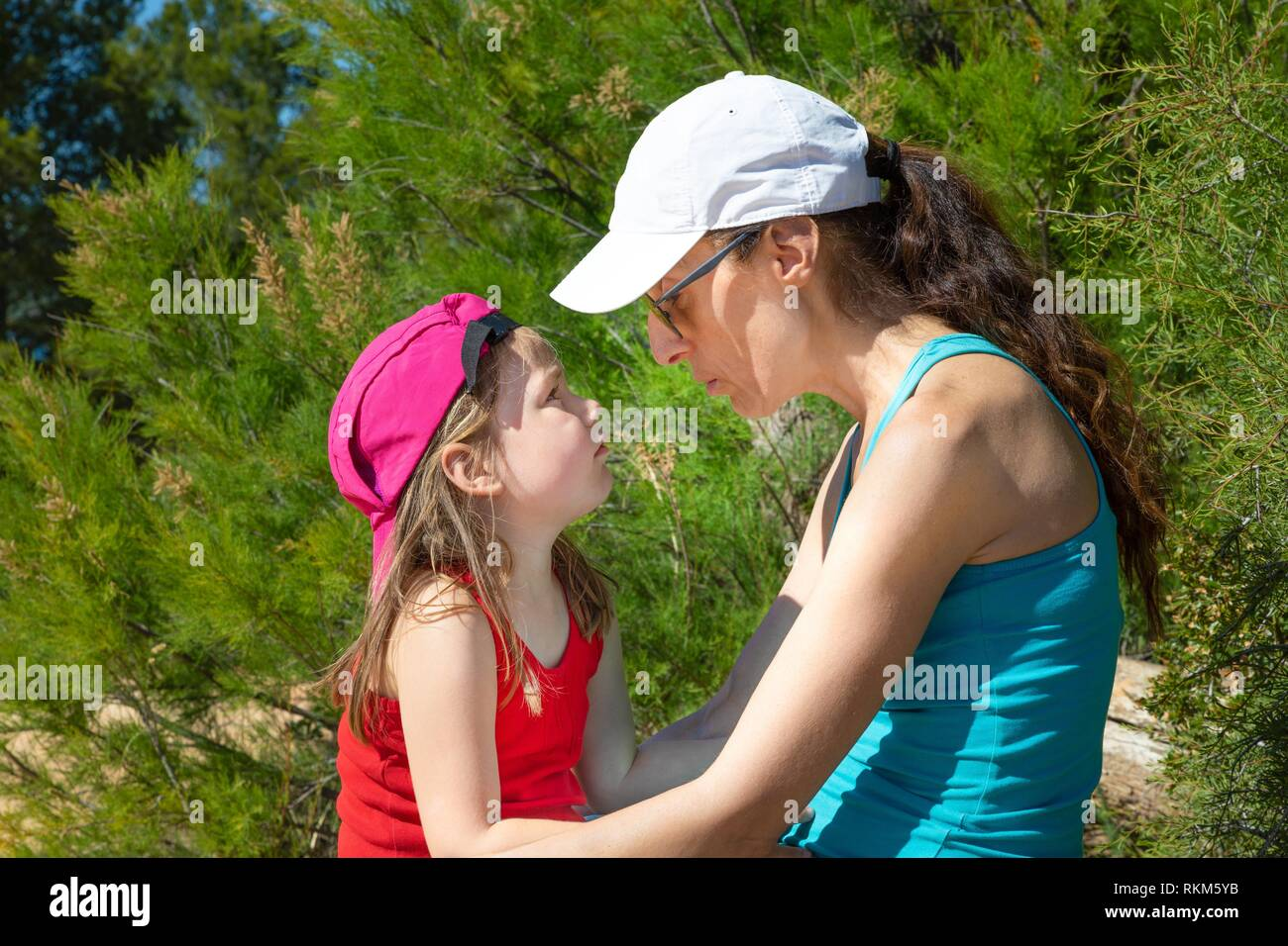woman talking to her daughter seriously, four years old blonde girl, both with caps, sitting in forest of the countryside. Stock Photo