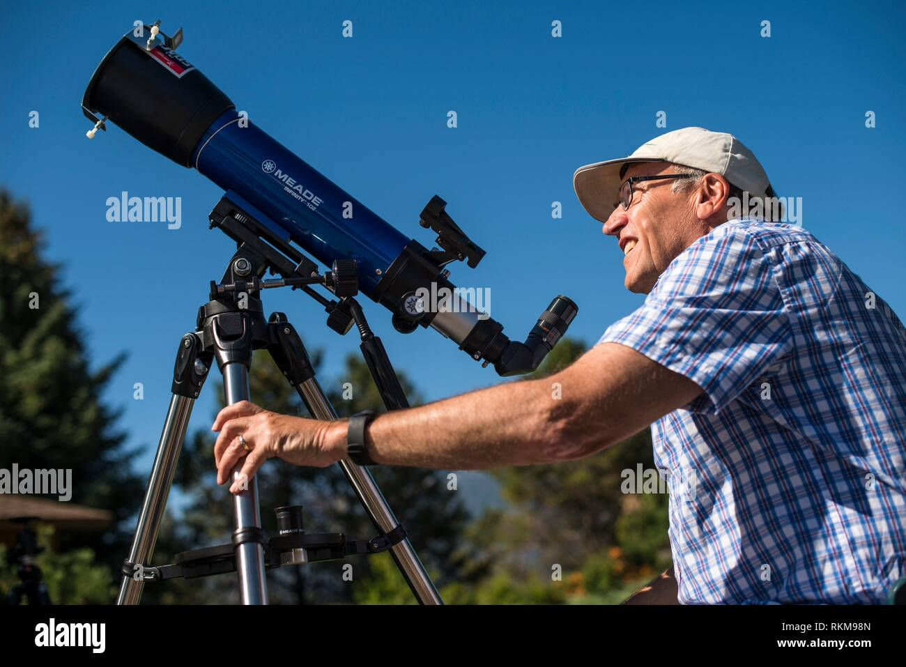 Man looking at solar eclipse with telescope - Stock Image