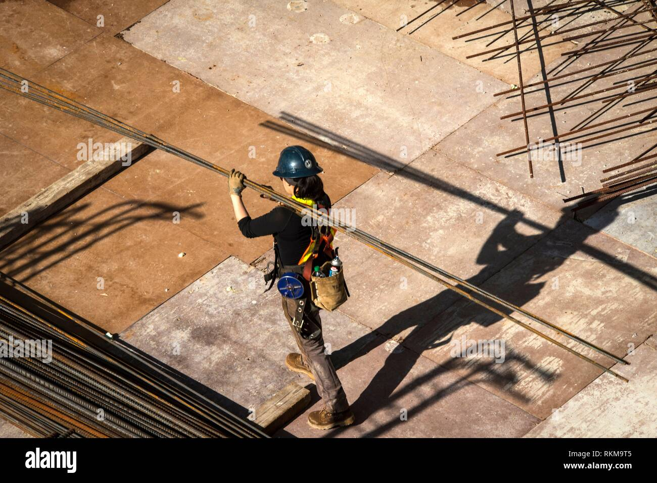 Construction worker carries steel bars at Vancouver House, a tower under construction in Vancouver, BC, Canada. Stock Photo