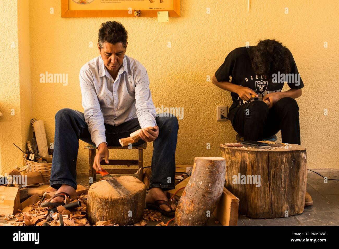 Two men sculpting alebrijes, folk art sculpture in Arrazola, Oaxaca, Mexico. - Stock Image