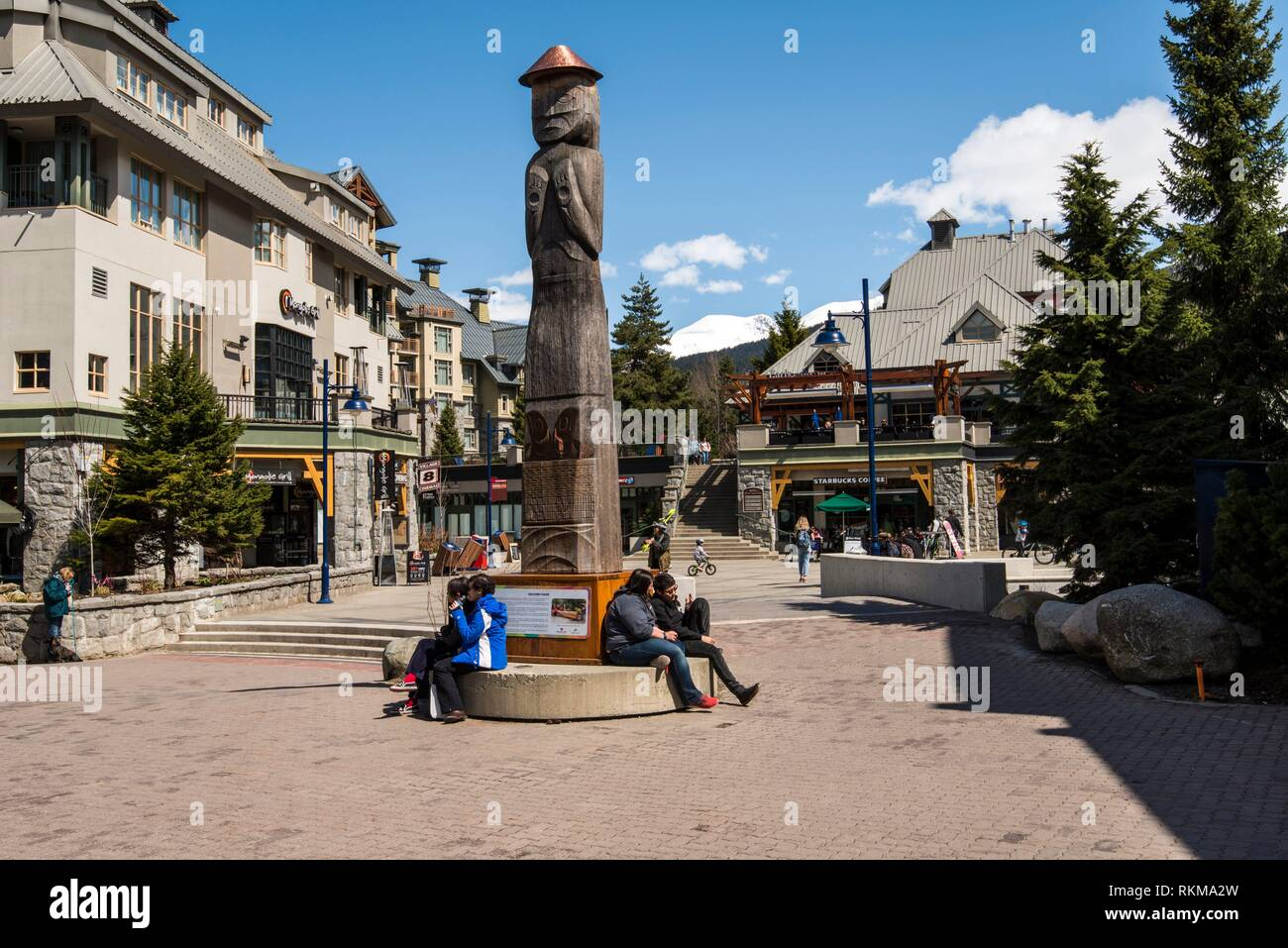People rest by a First Nations totem pole in Whistler village, British Columbia, Canada. - Stock Image