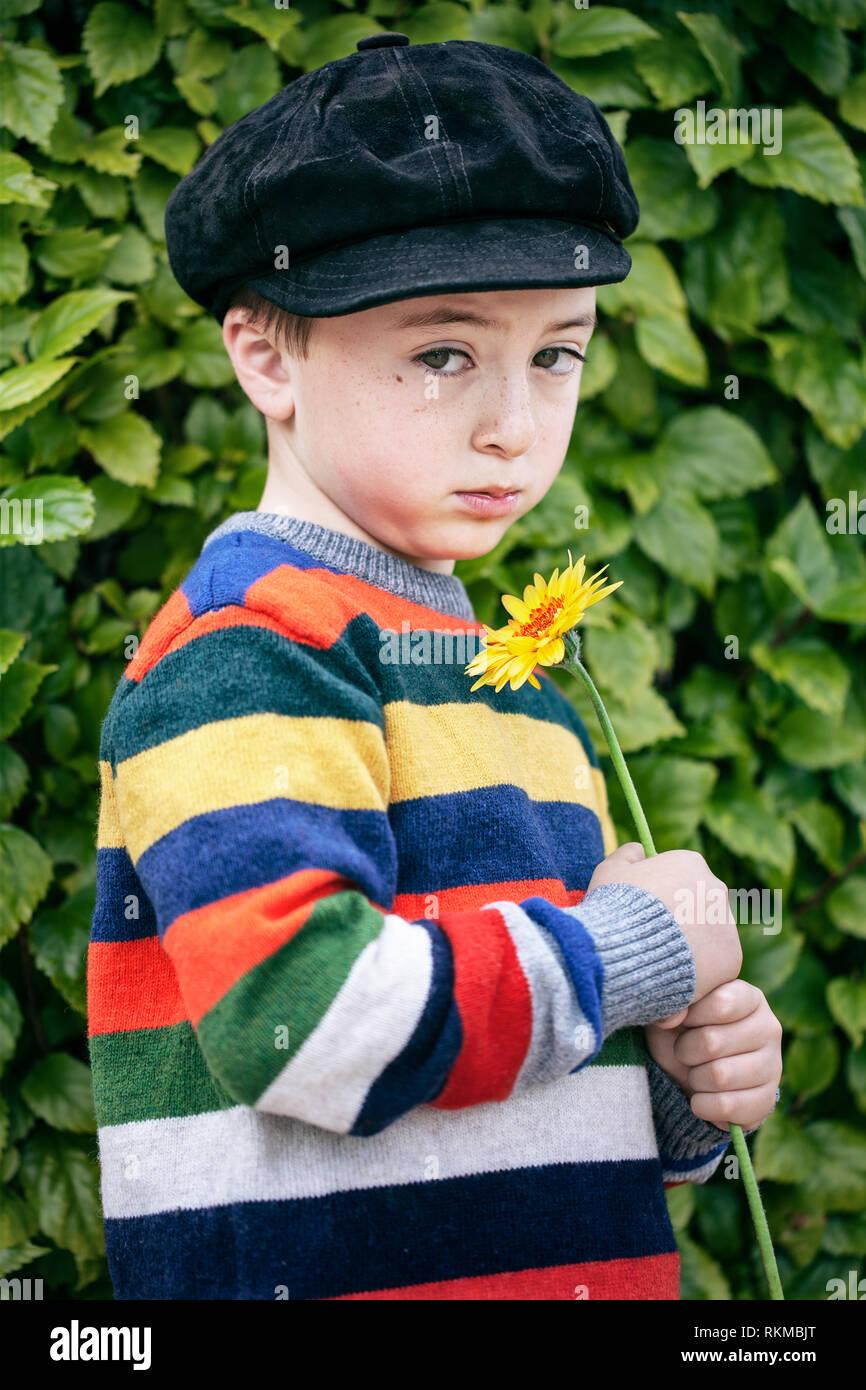 e1e3fc95 Sad, cute little boy in rainbow multicolored striped sweater and black  suede newsboy cap holding