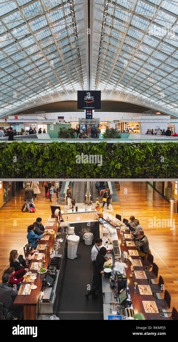 CDG Paris Airport - 12/22/18: Terminal 2F food court, huge skylight mesh with live vegetation, vertical garden and a bar. People travelling with suitc - Stock Image