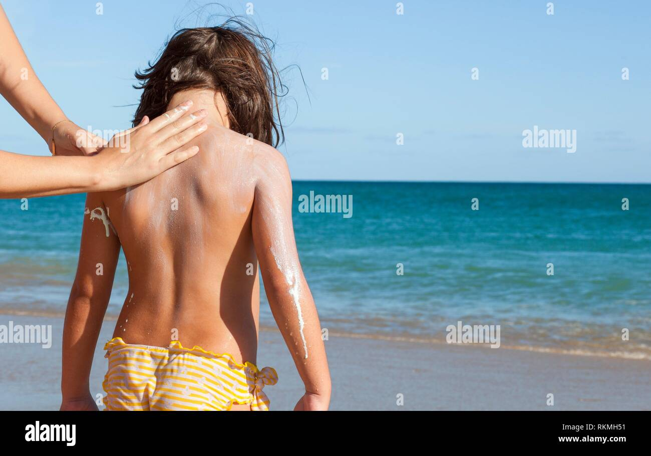 Mother applying sunblock cream to her daughter on nape. Idyllic beach background. - Stock Image