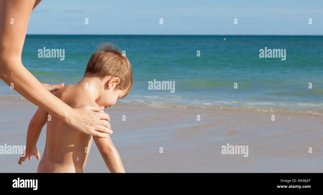 Mother applying sunblock cream to her little son on back. Idyllic beach background. - Stock Image