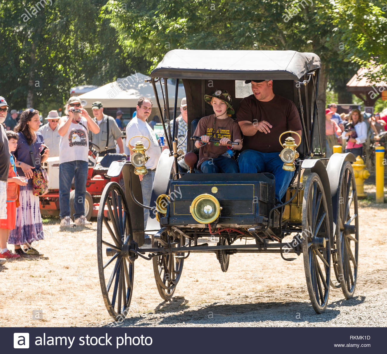Young boy driving an antique motor vehicle with supervision during the Great Oregon Steam-Up at the Powerland Heritage Park, Salem, Marion County, Ore - Stock Image