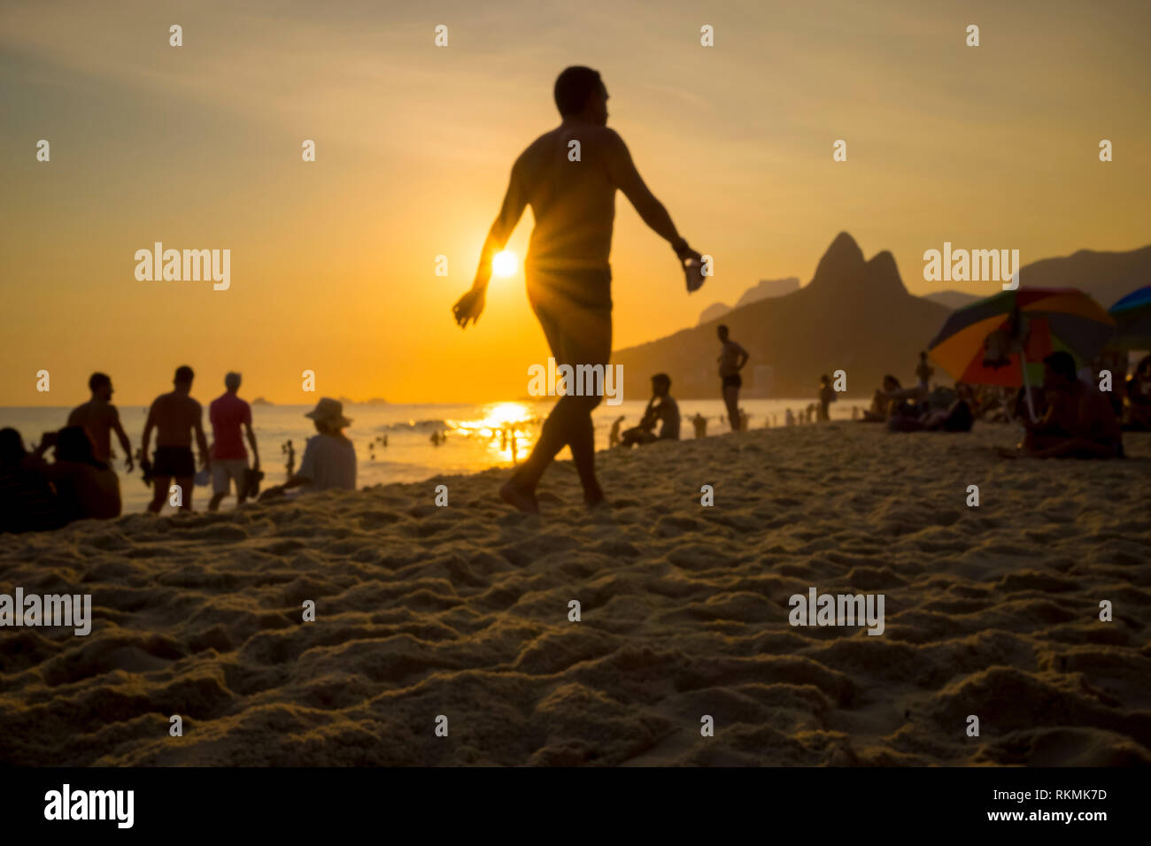 Beachgoers stroll and socialise on a summer afternoon on Ipanema Beach in Rio de Janeiro, Brazil - Stock Image