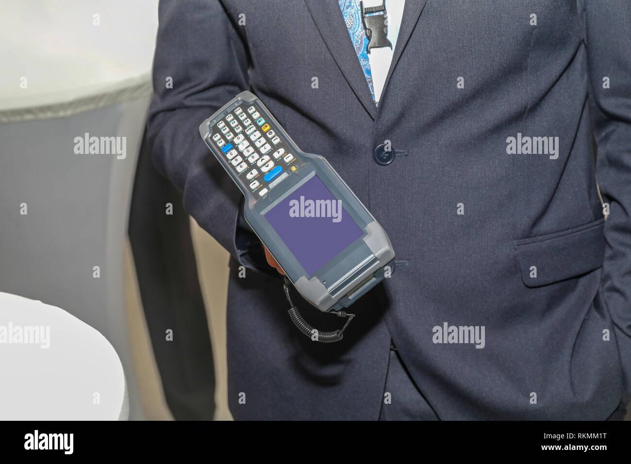 Man Holding Handheld Barcode Scanner Reader Portable Computer - Stock Image