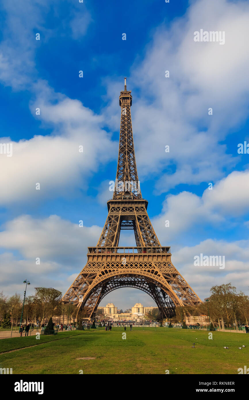 View of the Eiffel Tower or Tour Eiffel seen from Champ de Mars in Paris, France on a beautiful cloudy day Stock Photo
