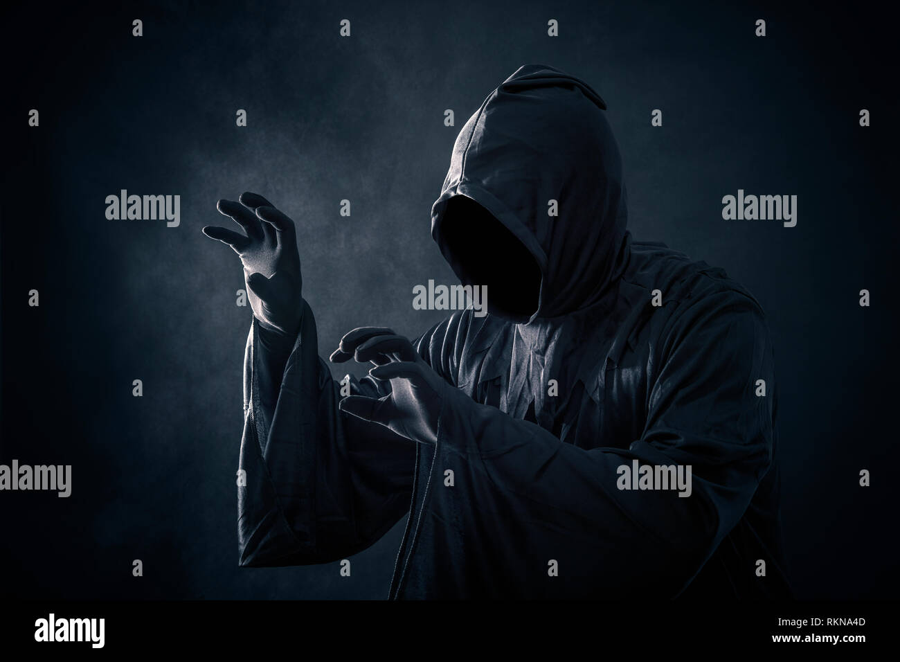 Scary figure in hooded cloak - Stock Image