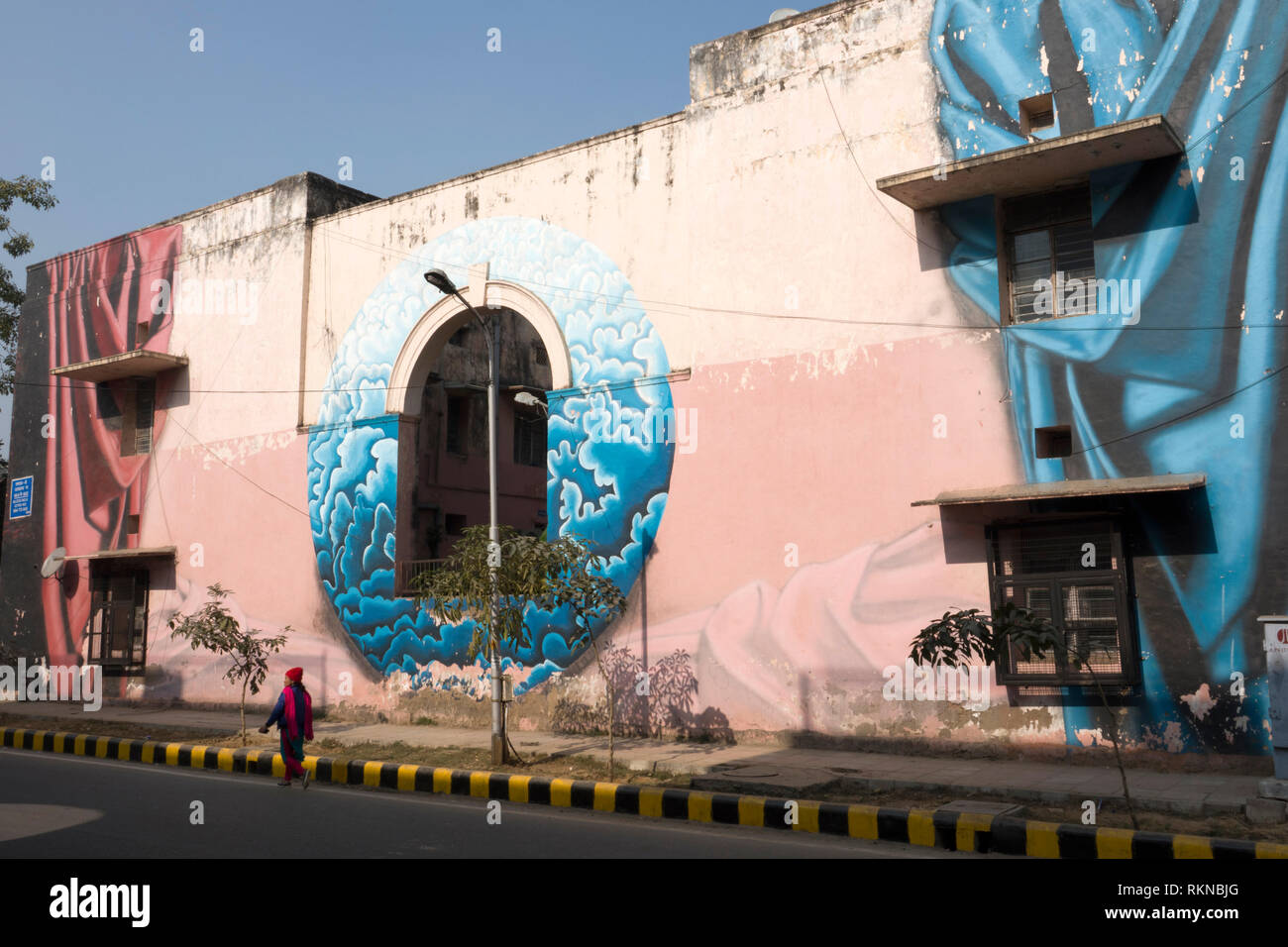 Woman walks past a large mural painted on side of building in Lodhi Colony, New Delhi, India - Stock Image
