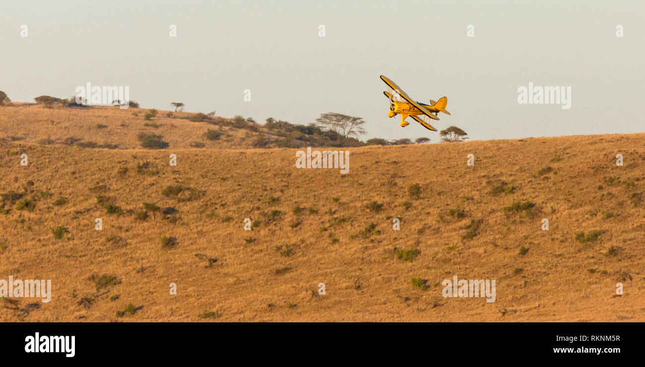 A 1930's Waco biplane flying at dawn over Laikipia, close to the hillside and banking, Lewa Wilderness,Lewa Conservancy, Kenya, Africa - Stock Image