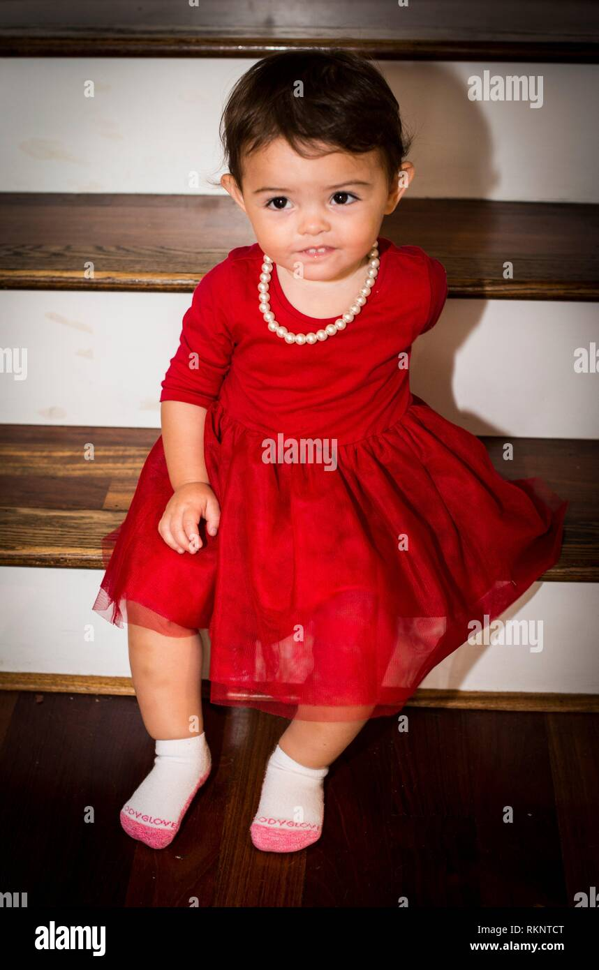 girl, 7 7/7 year old in red dress with pearl necklace Stock Photo