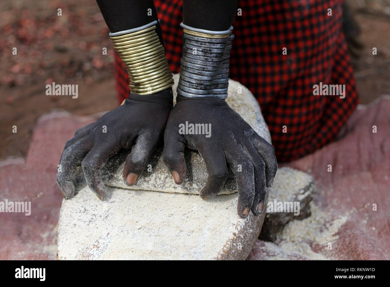 Close-up of Mursi woman kneeing down and making flour the traditional way with stone, Ethiopia, East Africa. - Stock Image