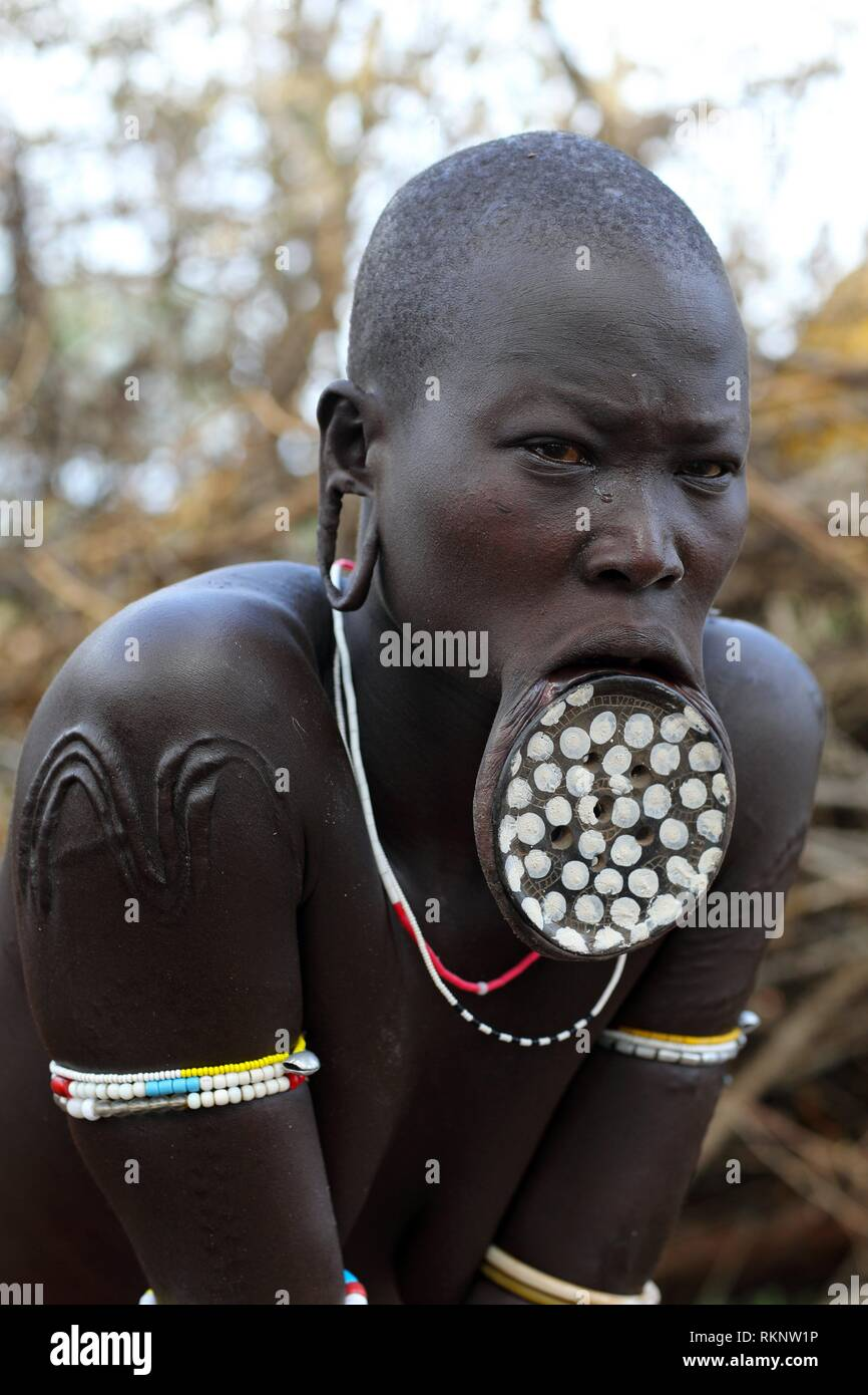 Portrait of Mursi woman with huge lip plate, looking at the camera, Ethiopia, East Africa. - Stock Image