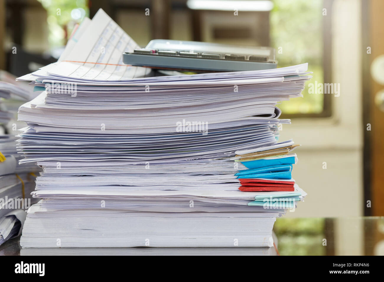 Close up of business papers stack on desk. Pile of unfinished documents on office desk - Stock Image