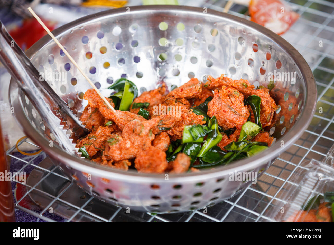Tod Mun Pla Krai, Thai Deep Fried curried clown knifefish cake with crispy crunchy fried holy basil leaves and sweet cucumber and coriander dipping sa - Stock Image