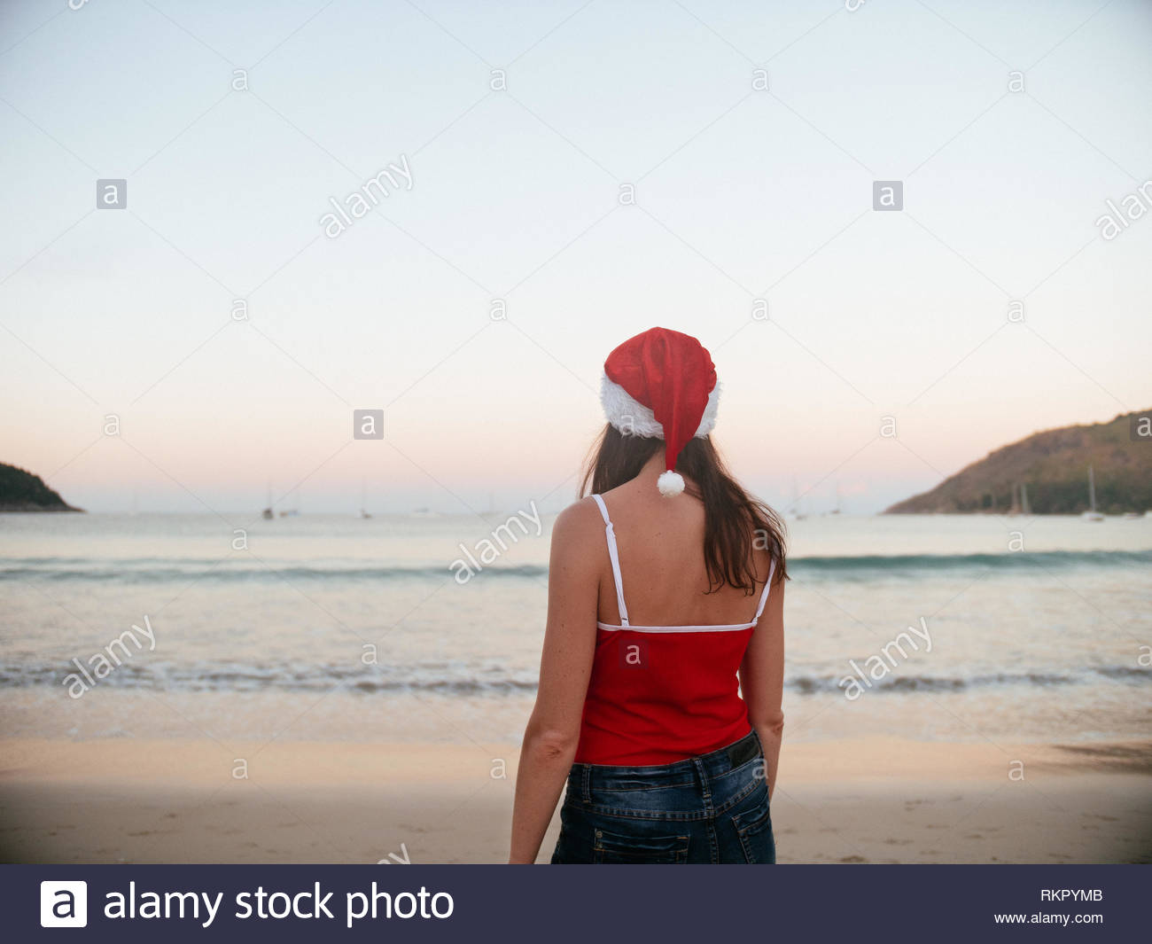ffa8224dee5 Rear view of carefree woman happy in santa hat and red swimsuit enjoying  sunset on the tropical paradise beach. Vacation