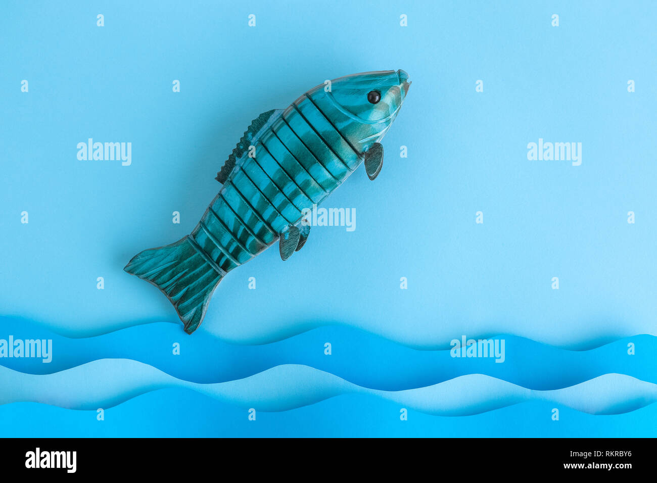 Flat lay of fish jumping out of the ocean minimal creative concept. Space for copy. - Stock Image