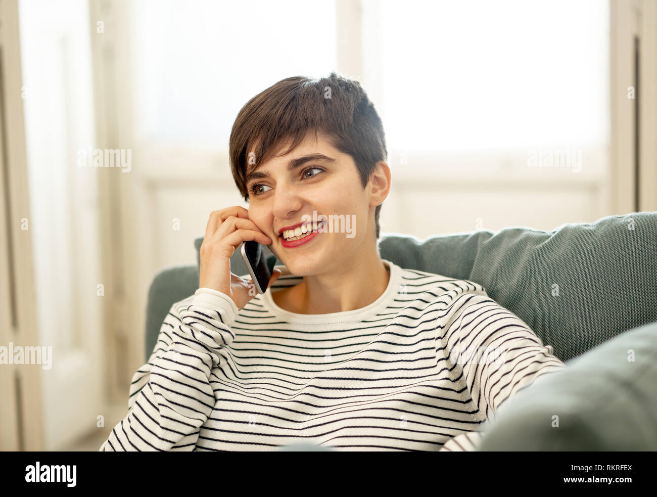 Happy attractive young woman on smart mobile phone chatting