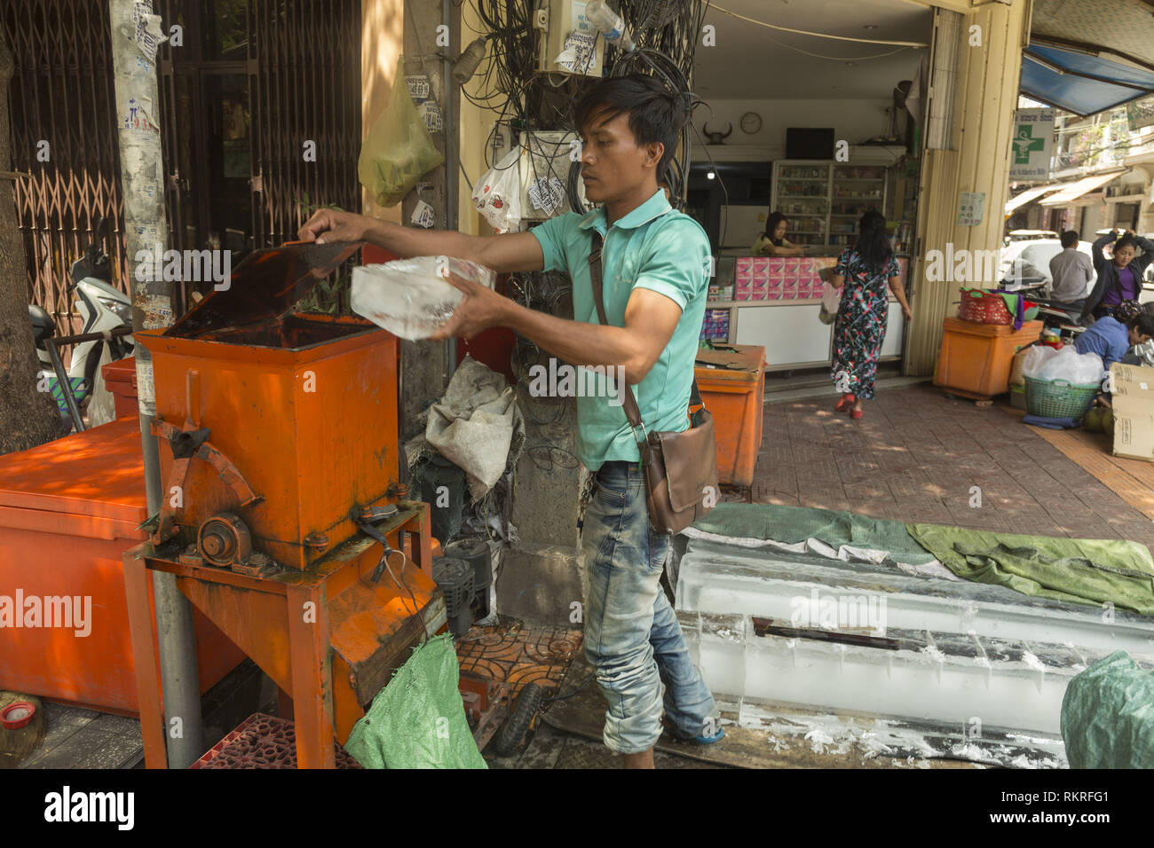 Breaking ice blocks with machine on the street in Phnom Penh Stock Photo
