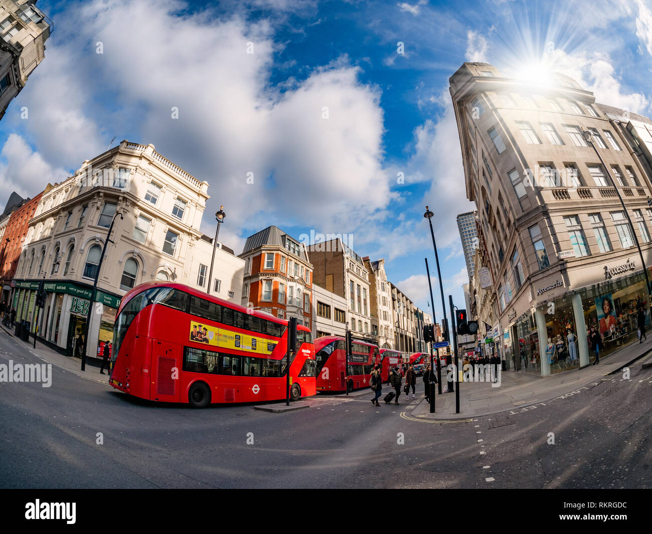 London, UK - February 11, 2019: British architecture on Oxford street in the main center area of London, with traditional red buses transporting touri - Stock Image