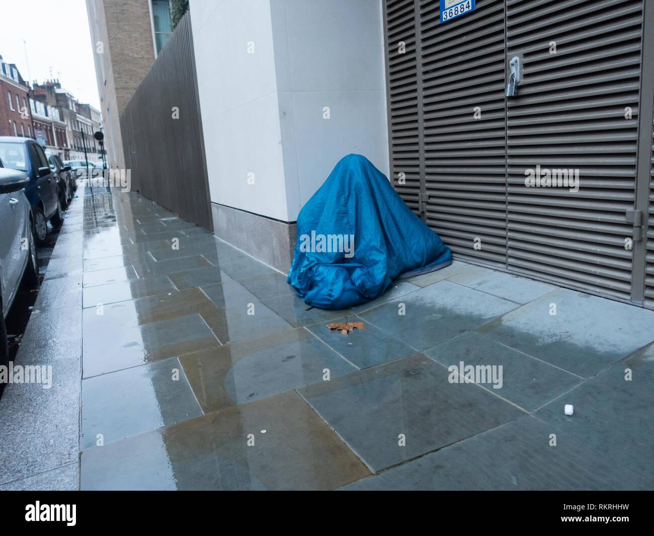 Homeless Person Under Sleeping Bag Stock Photo