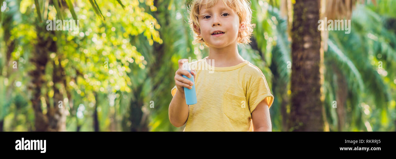 Boy spraying insect repellents on skin BANNER, long format - Stock Image
