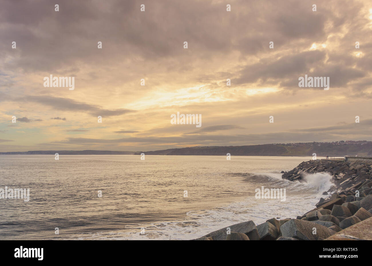 A wave breaks on the rocks at Scarborough in winter. A headland is in the distance and a dramatic cloud formation is above. - Stock Image