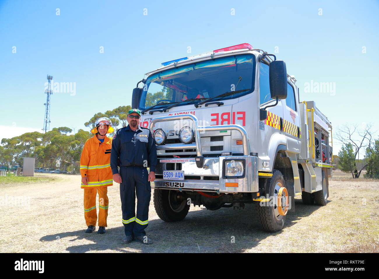 Two Firemen pose in front of their fire engine in Milang, South Australia at the Power Rally at Port Milang, South Australia - Stock Image