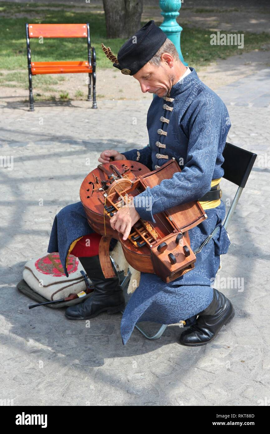 BUDAPEST, HUNGARY - JUNE 20, 2014: Street performer plays hurdy-gurdy in Budapest. Hurdy-gurdy is a traditional string instrument also known as wheel  Stock Photo