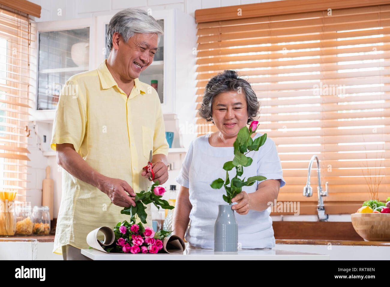 Asian Senior couple husband and wife flower arrangement to vase on table in kitchen at home in Valentine's Day.lovely senior couple concept Stock Photo