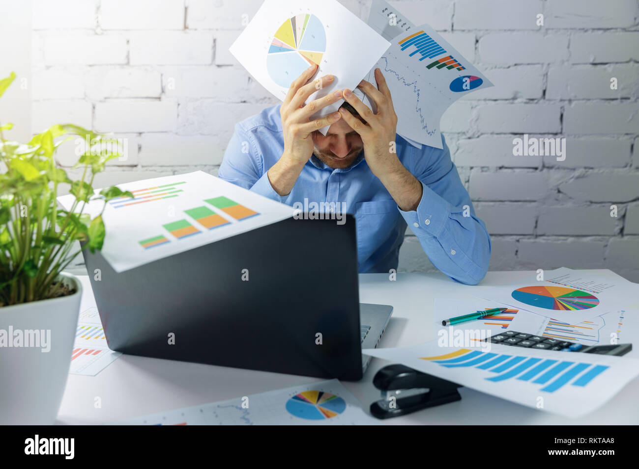 desperate overworked businessman doing paperwork in office - Stock Image