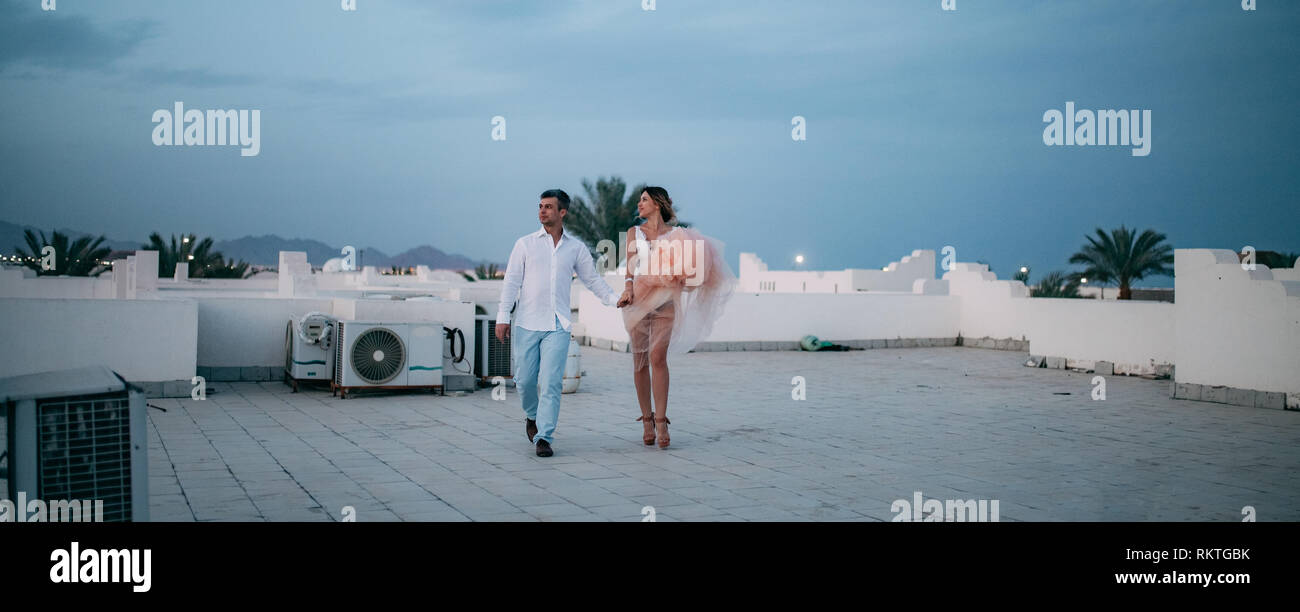 Happy newlyweds walk holding hands on roof of house during the honeymoon in Egypt in the evening. - Stock Image