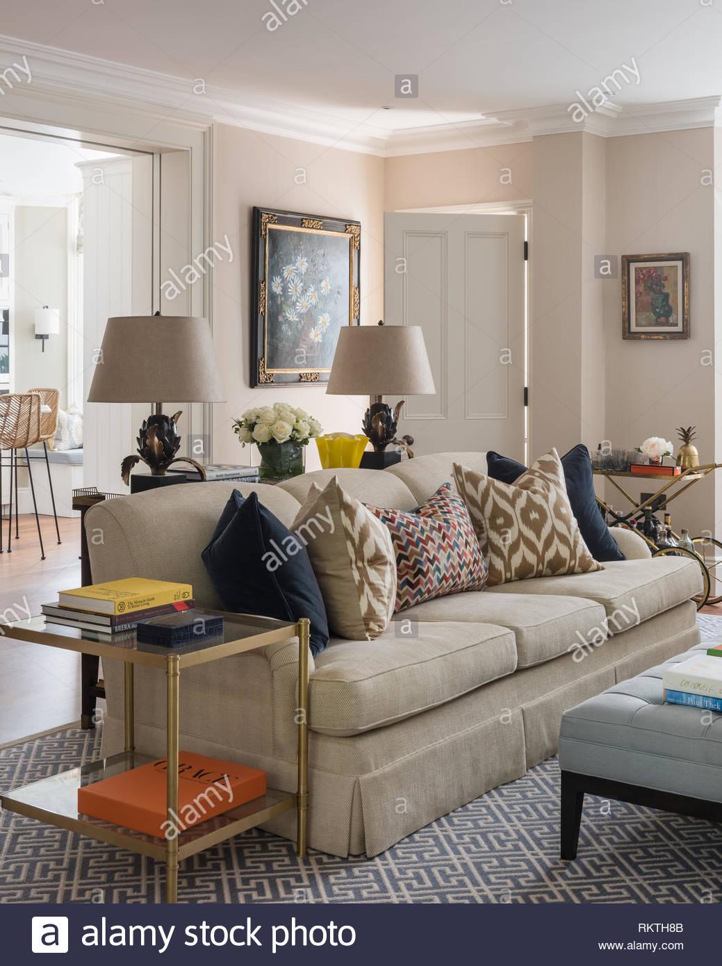 Ikat cushions on cream sofa in Kensington home - Stock Image