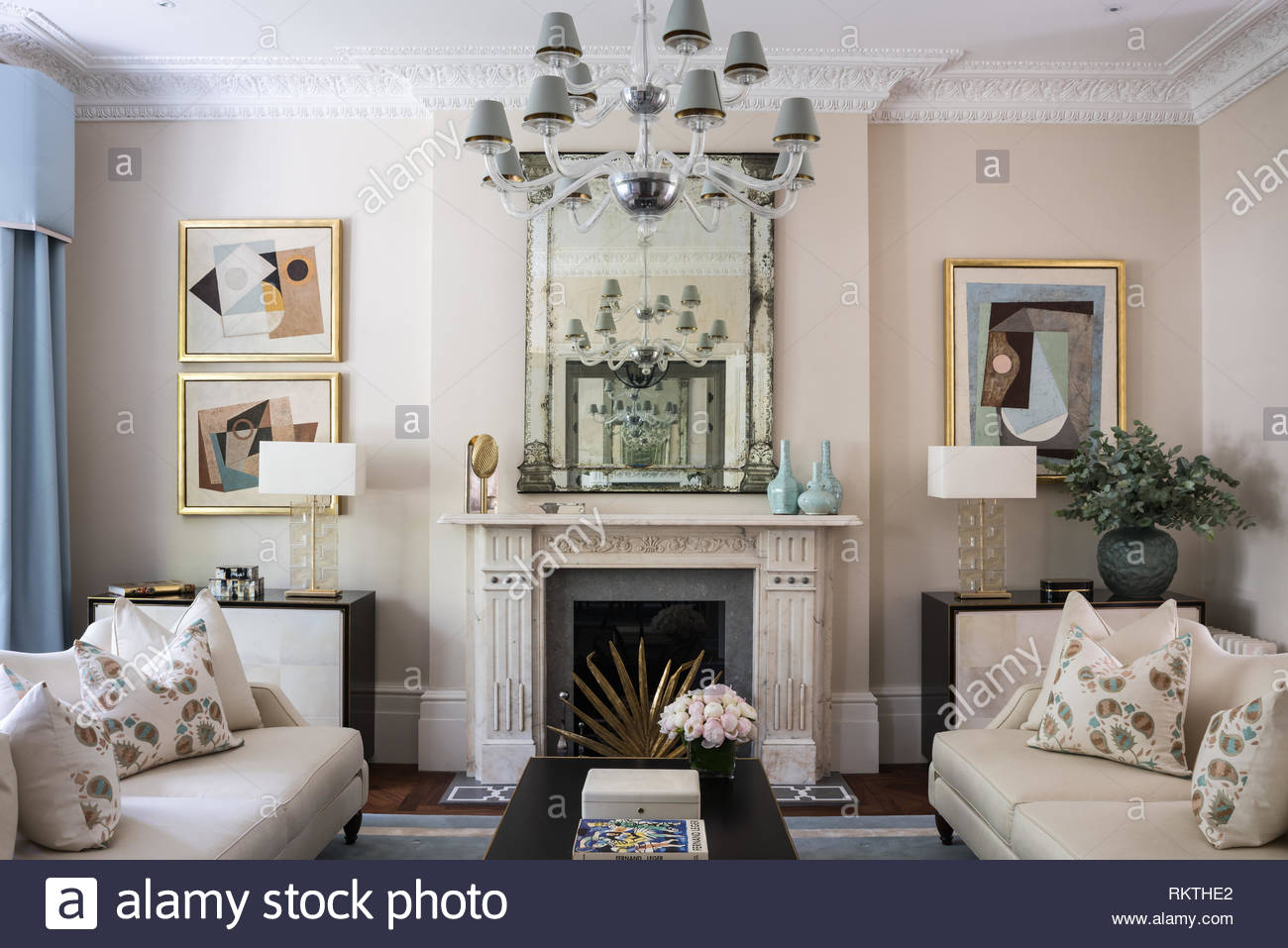 Symmetrical living room with vintage mirror above fire - Stock Image
