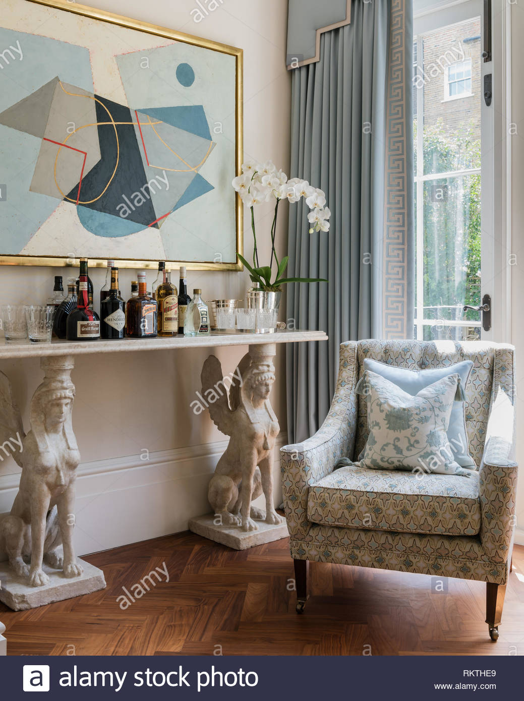 Large artwork by Jeremy Annear above marble topped drinks shelf with caryatid sphinx and an upholstered armchair - Stock Image