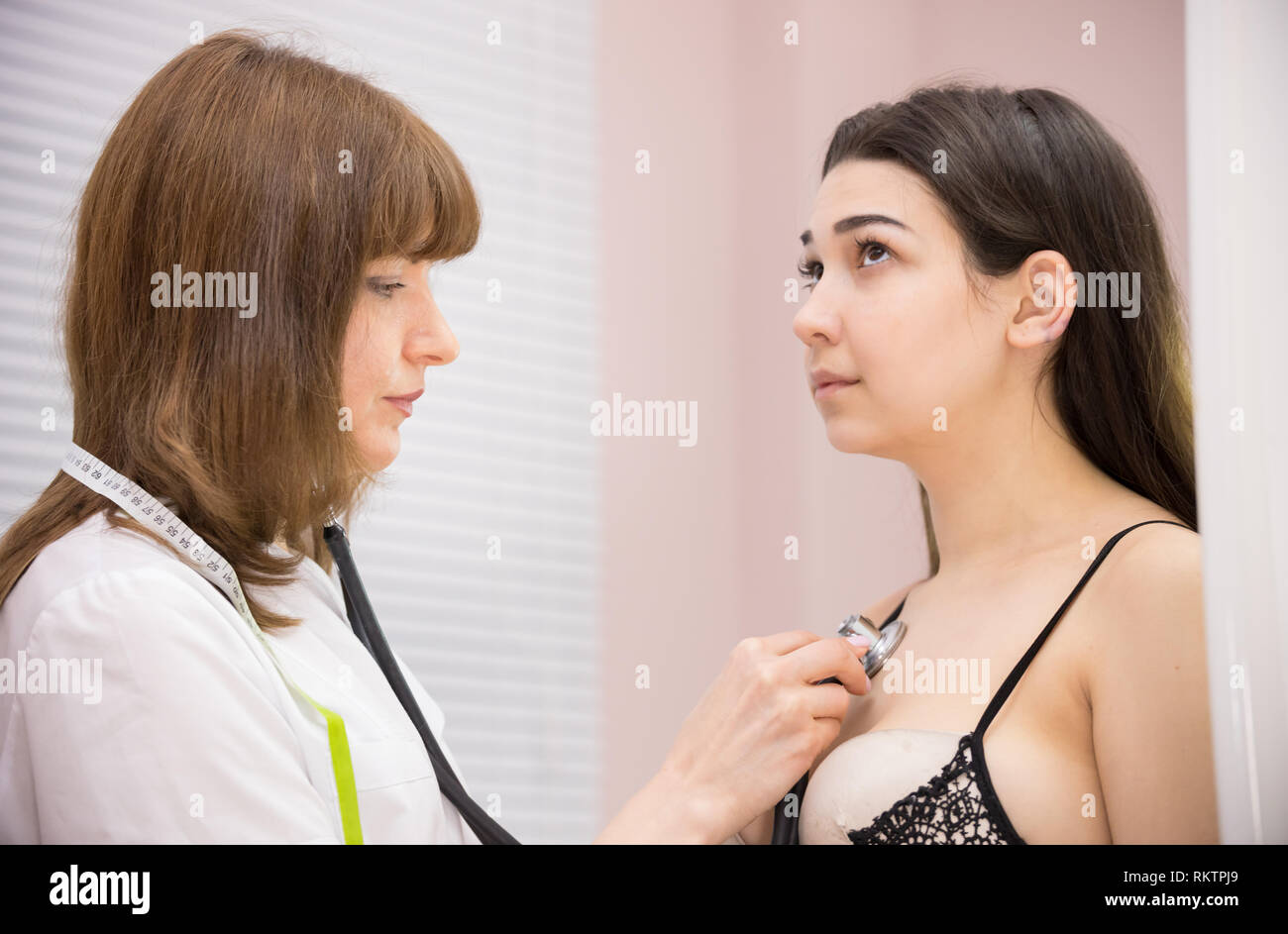 cosmetology beauty clinic. doctor hearing patient's heart beating - Stock Image