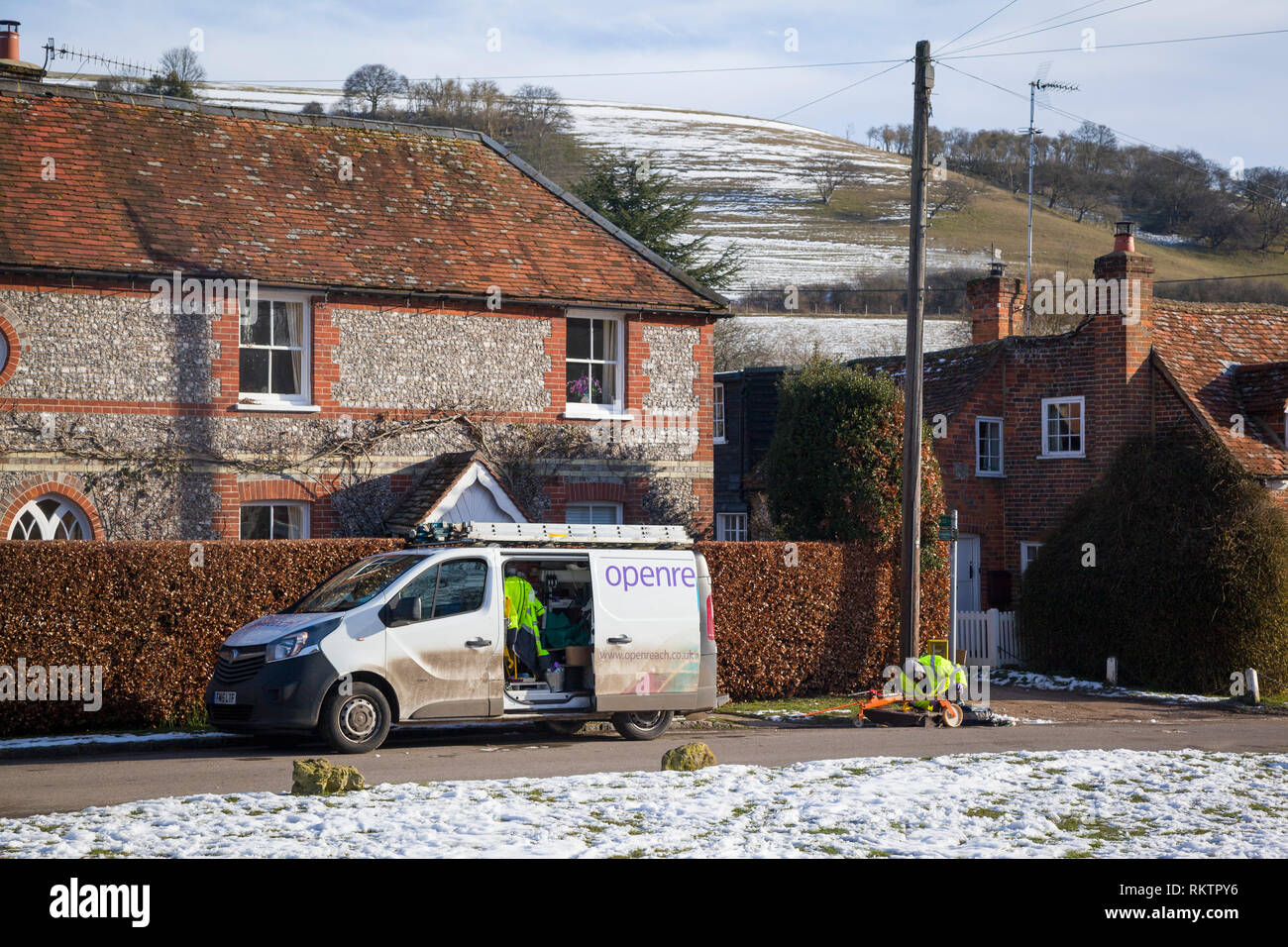 A BT OpenReach engineer repairs a telephone line in the snow covered village of Turville, Buckinghamshire. - Stock Image