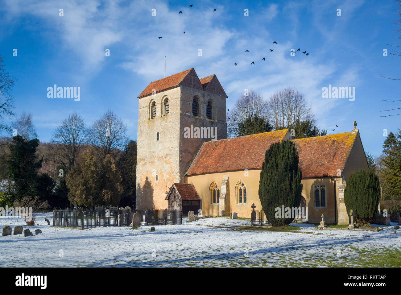 The Parish Church of St. Bartholomew's in Fingest with a light covering of snow and Jackdaws flying back to roost in the tower. - Stock Image